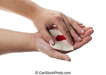 human hand applying white medicine bandage on wound