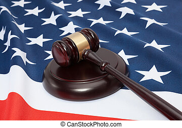 Close up shot of a judge gavel over United States flag -...