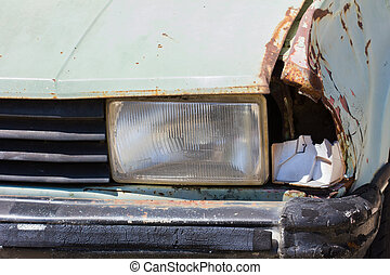 Close up shot of a junked car left in a car park.