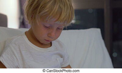 Close up shot of a little boy sitting in his bed at night plays a tablet pc with silhouettes of a skyscraper at a background
