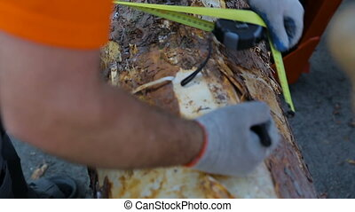 Close up shot of a male carpenter using a measuring tape and a pencil to mark a length on wooden deck