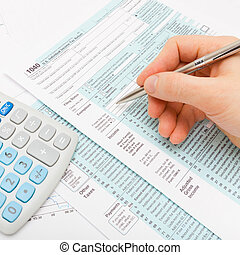 Close up shot of a male filling out US 1040 Tax Form with calculator next to it