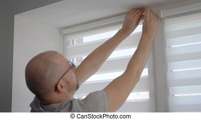 Close up shot of a man installing new blinds on his window in apartment.