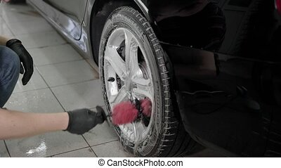 Close up shot of a man washing car disks in carwash.