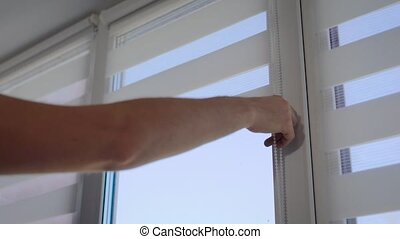 close up shot of a man's hand, who lowers the blinds with a...