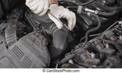 Close-up shot of a mechanic checking oil in car's engine,...