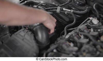 Close-up shot of a professional car mechanic fixing a part...