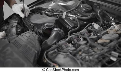 Close-up shot of a professional car mechanic fixing a part...