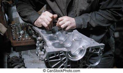 Close up shot of a professional mechanic disassembling...