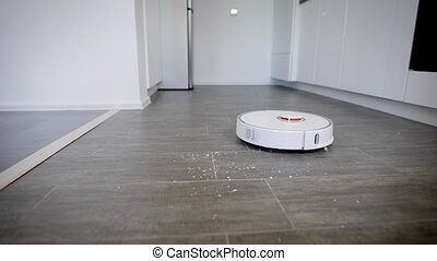 Close up shot of a robot vacuum cleaner cleaning kitchen...