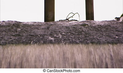 Close up shot of a small man made canal with a branch stuck