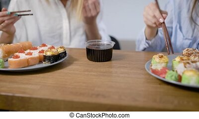 Close-up shot of a two plates of different sushi rolls, girl eating sushi with chopsticks.