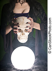 Close-up shot of a witch with long nails holding human skull