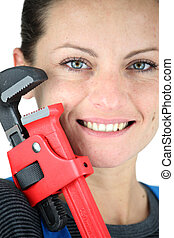 Close-up shot of a woman holding a pipe wrench