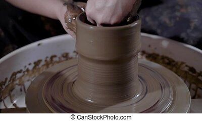 close up shot of a woman's hands, who engages in pottery, a man wants to make a vase of clay in the workshop