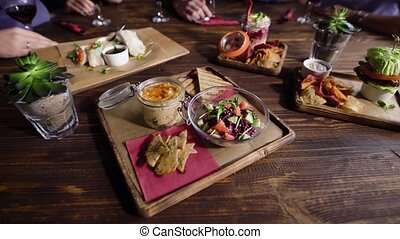 Close up shot of a wooden table with vegetarian snacks that are beautifully decorated and served by the waiter. Different vegetables lie in plates, sauces in bowls