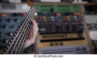 Close up shot of ambitious musician holding a bass guitar in...