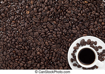 Close-up shot of baked coffee beans and coffee cup with black coffee.