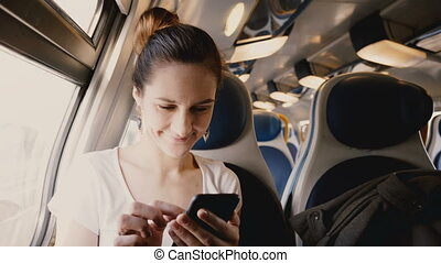 Close-up shot of beautiful happy European girl using smartphone social network app traveling on train window seat.