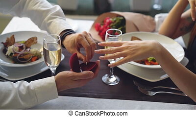 Close-up shot of beautiful ring being placed on female finger during marriage proposal at romantic dinner in restaurant. Engagement and fine dining concept.