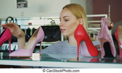Close-up shot of blond young woman choosing high-heel shoes...