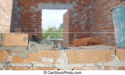 Close-up shot of Bricklayer builds wall into house.