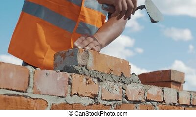 Close-up shot of Bricklayer builds wall.