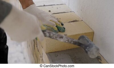 Close up shot of builder laying bricks on the mortar indoor....