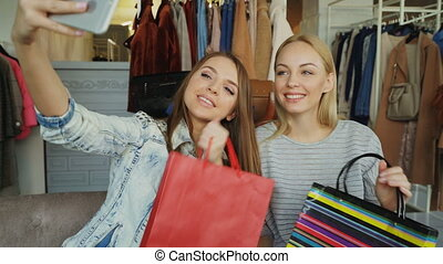 Close-up shot of cheerful girls with paper bags making selfie with smartphone while sitting in clothes department in mall. First they are posing, then checking pictures