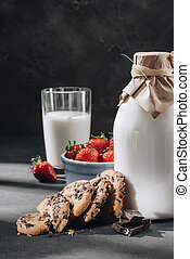 close-up shot of chocolate-chip cookies with milk and strawberries