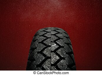 Close-up shot of classical motorcycle tire tread in wet...