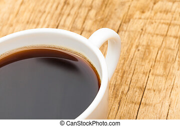 Close up shot of coffee cup on wooden table