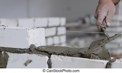 Close up shot of construction worker laying white bricks for...