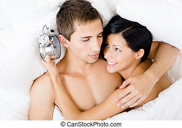 Close up shot of couple lying in bed with alarm clock