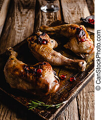 close-up shot of delicious grilled chicken legs on wooden board