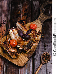 close-up shot of delicious grilled ribs on wooden cutting board