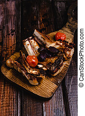 close-up shot of delicious grilled ribs with tomatoes on wooden cutting board