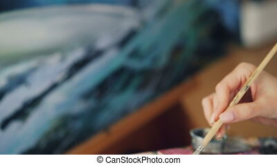 Close-up shot of dirty female hand holding paintbrush and...