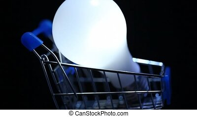 close-up shot of electric lamp in toy shopping trolley rotating on black