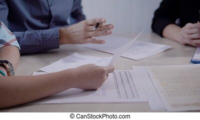Close up shot of estate agent showing contract for buying house to the married couple in the office.
