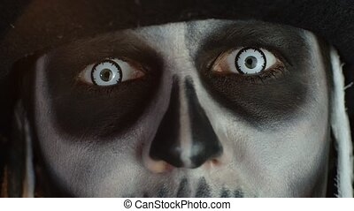 Close-up shot of face in skeleton Halloween makeup opening ...