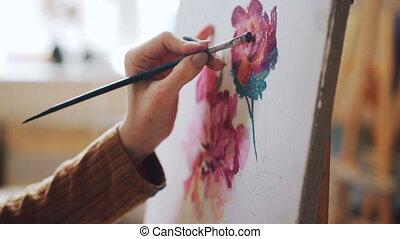 Close-up shot of female hand holding paintbrush and painting...