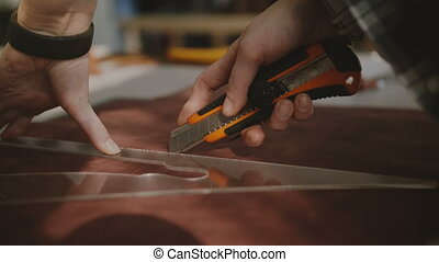 Close-up shot of female hands cutting pieces out of leather...