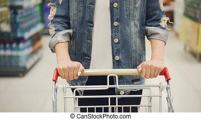 Close-up shot of female hands pushing shopping cart in...