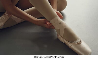 Close-up shot of girl's feet in ballet slippers and hands trying to put on footwear and tie ribbon around leg beautifully. Pointe-shoes, dancing and attire concept.