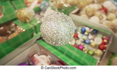 Close-up shot of glistening silver ball, rotating toy for a Christmas tree.