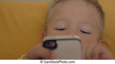 Close-up shot of little boy playing a game on the smartphone