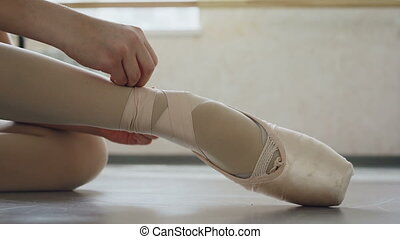 Close-up shot of little girl's foot in pointe shoe and hands...