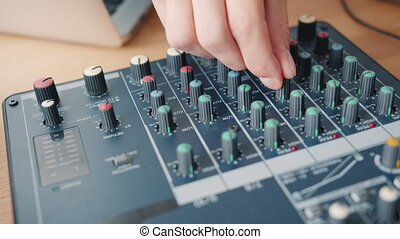 Close-up shot of male hand adjusting sound using modern audio equipment on table in recording studio. Contemporary technology, people and electronics concept.