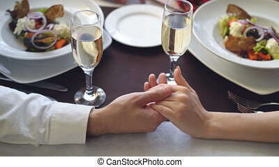 Close-up shot of male hand holding and caressing female hand on table with champagne glasses and plates. Romantic relationship, love and fine dining concept.
